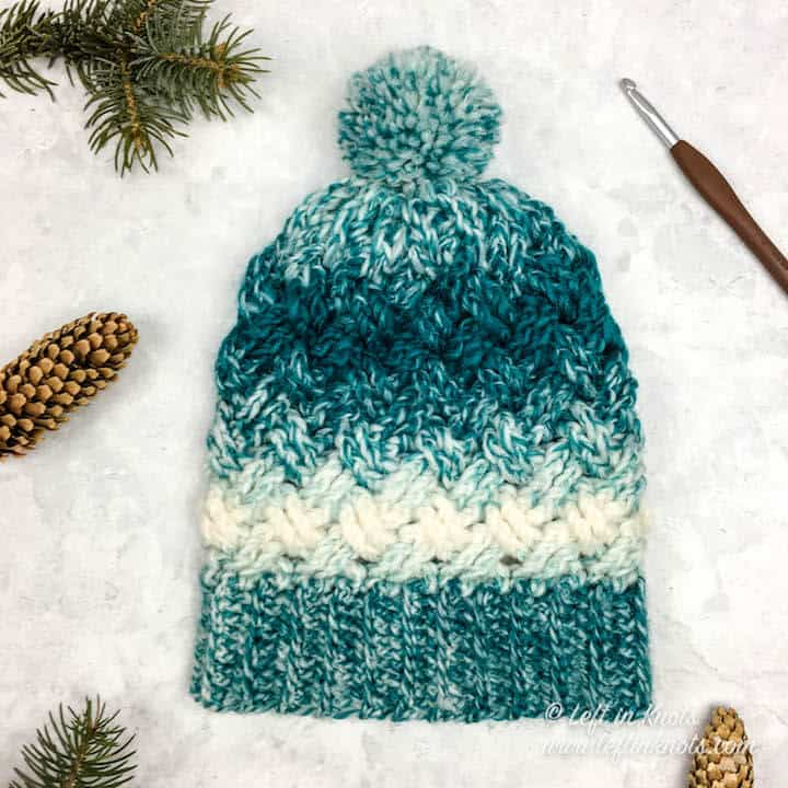 A teal and cream crochet beanie made with the Celtic Weave stitch