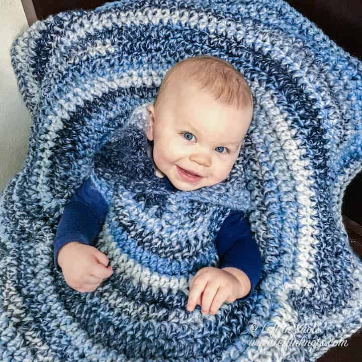 A crochet car seat poncho for toddlers made with chunky yarn