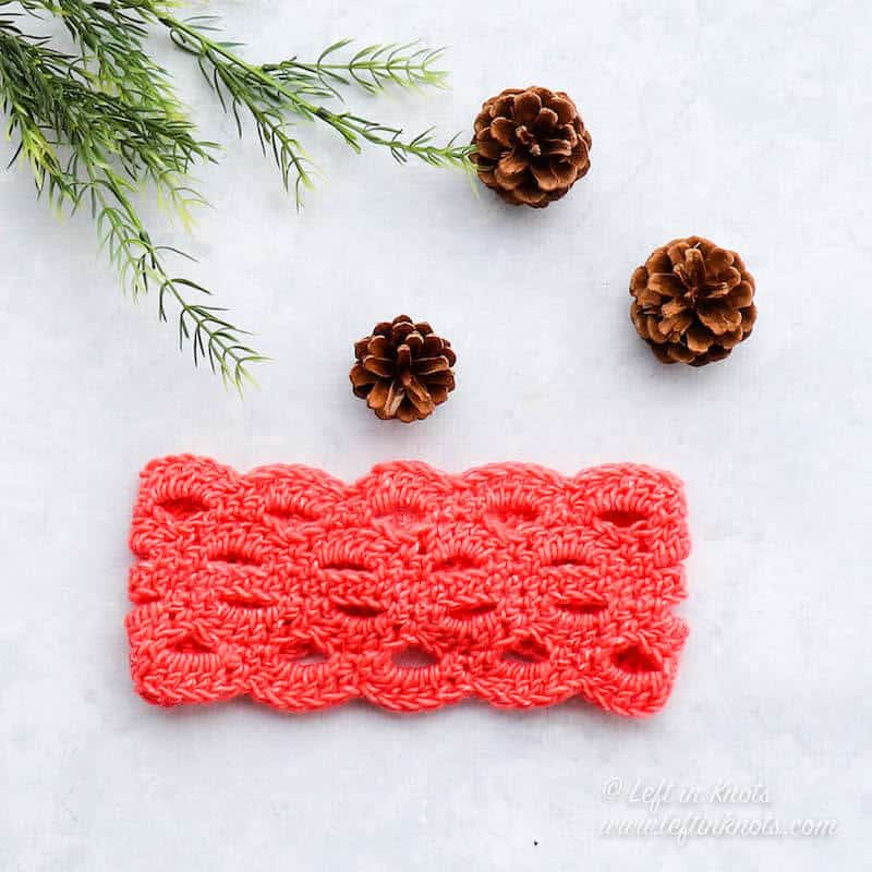 A lacy coral crochet headband made with the arcade stitch