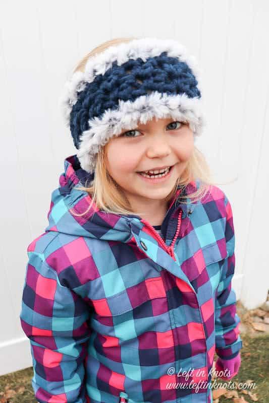 A girl wearing a blue chunky crochet ear warmer trimmed with faux fur