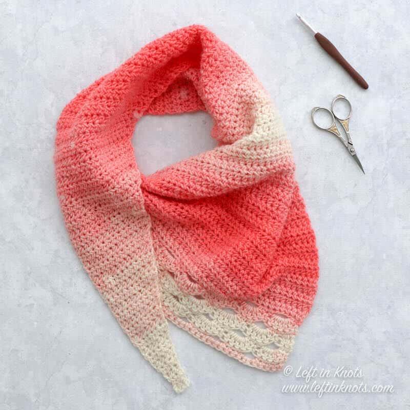 A coral and cream asymmetrical crochet scarf using the arcade stitch
