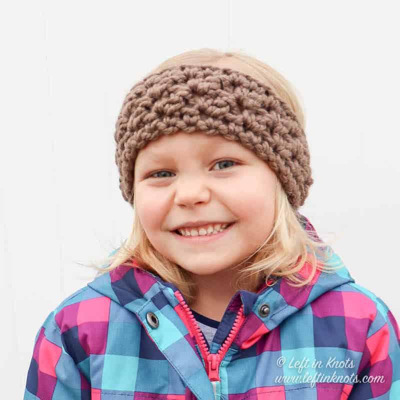 A girl wearing a taupe chunky crochet ear warmer