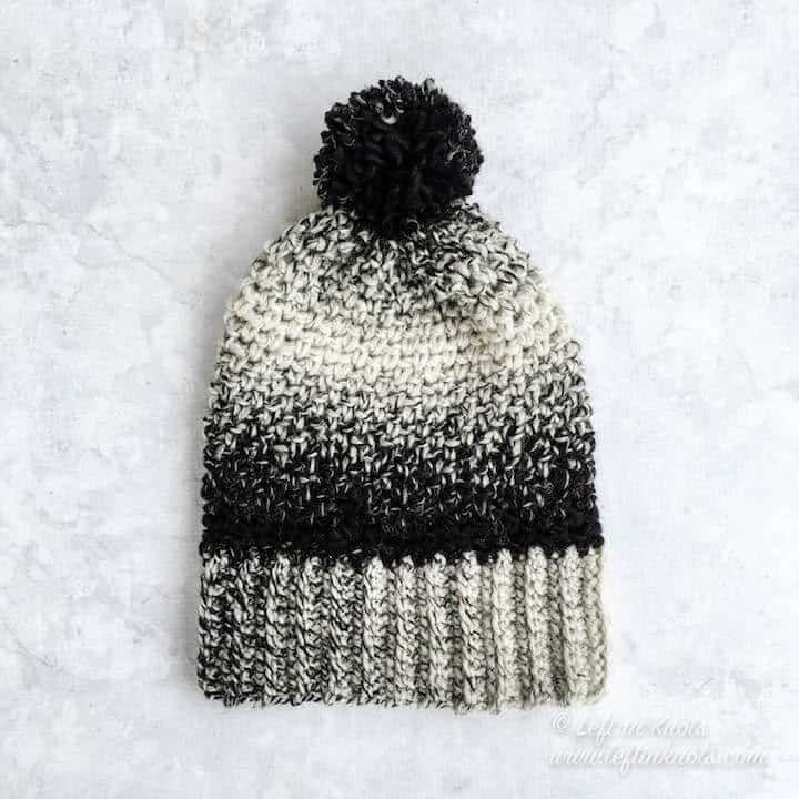 A black and white crochet beanie made with the moss stitch