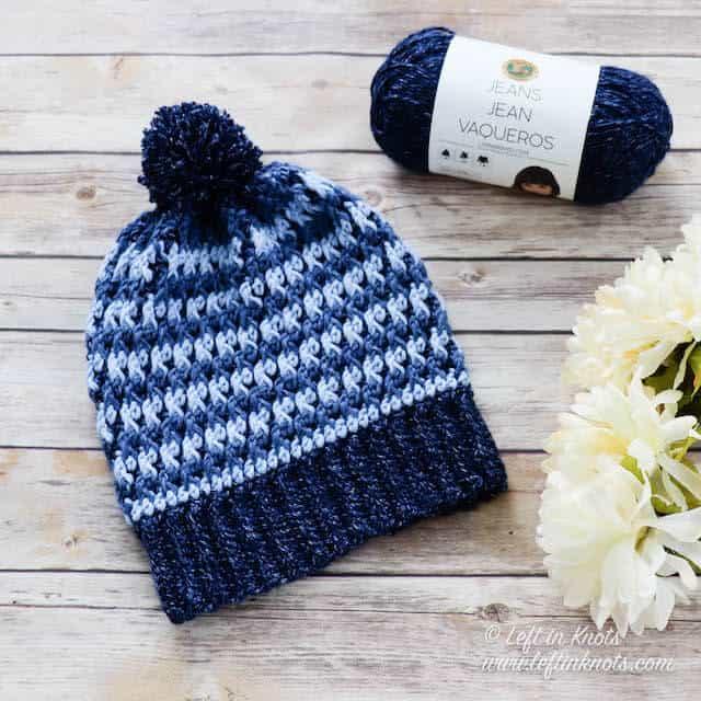 A denim blue crochet beanie made with the alpine stitch