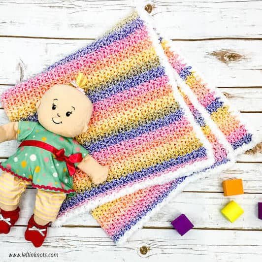 An easy striped crochet baby blanket with a white fuzzy border