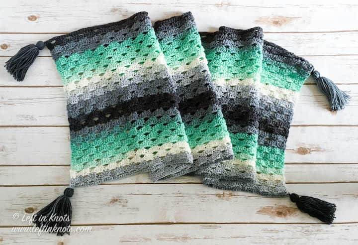 A mint and gray crochet rectangle wrap made with the arcade stitch