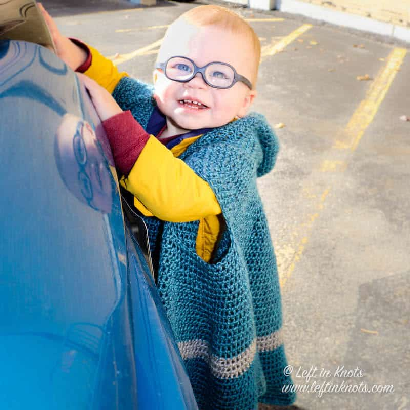A hooded crochet car seat blanket for toddlers