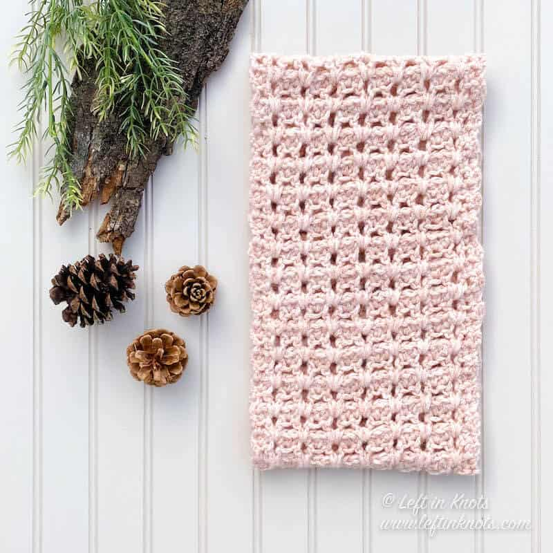 A blush crochet cowl made with chainette yarn
