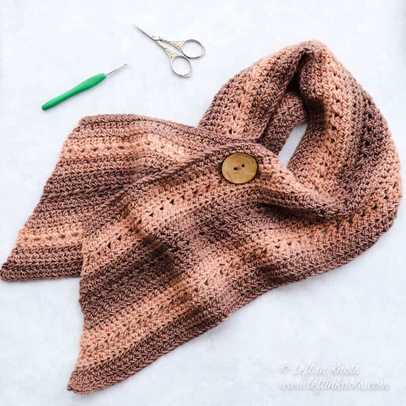 A wide crochet wrap scarf with button