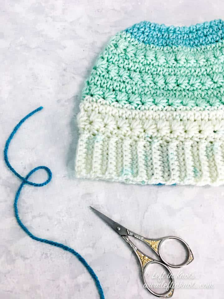 A crochet messy bun beanie made with the star stitch