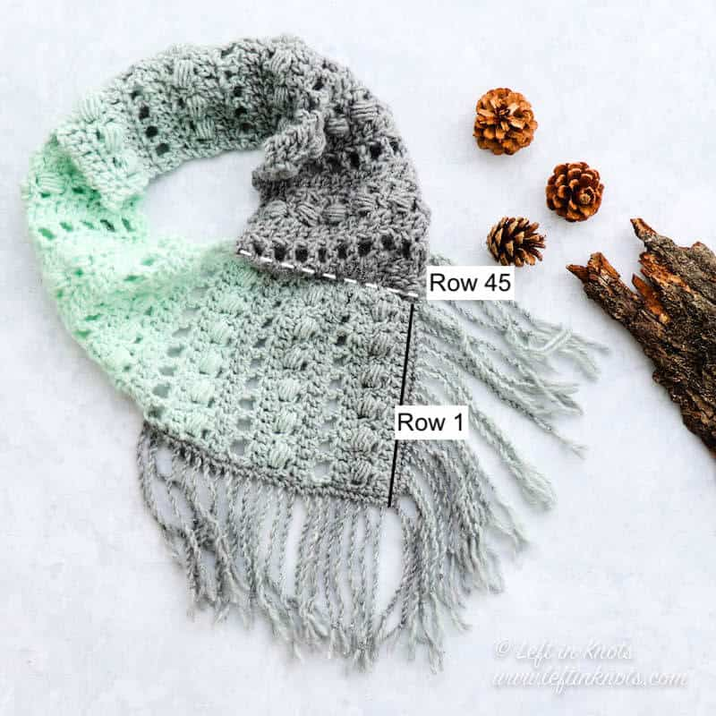 A gray and mint bandana style crochet cowl with fringe