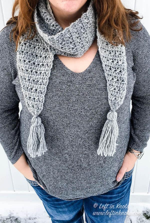 A gray and cream scarf with angled edges and tassels