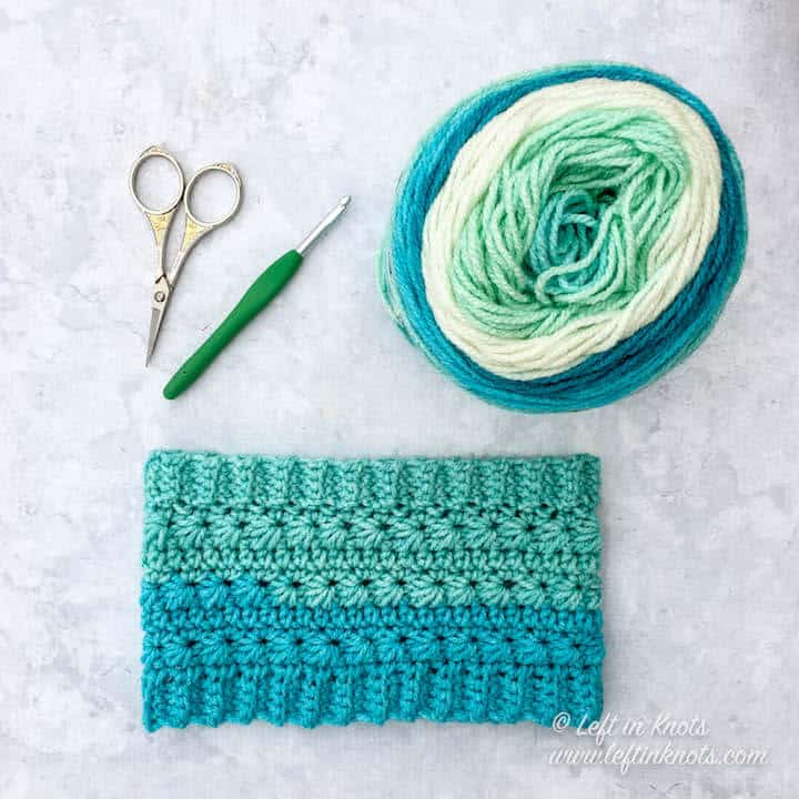 A crochet ear warmer made with the star stitch and Caron Cakes yarn