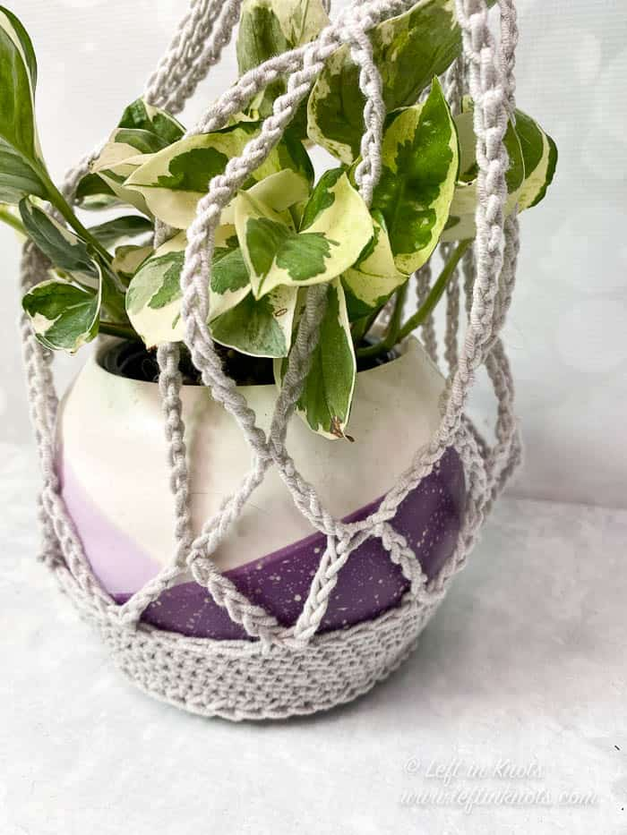 A gray crochet plant hanger made with cotton yarn