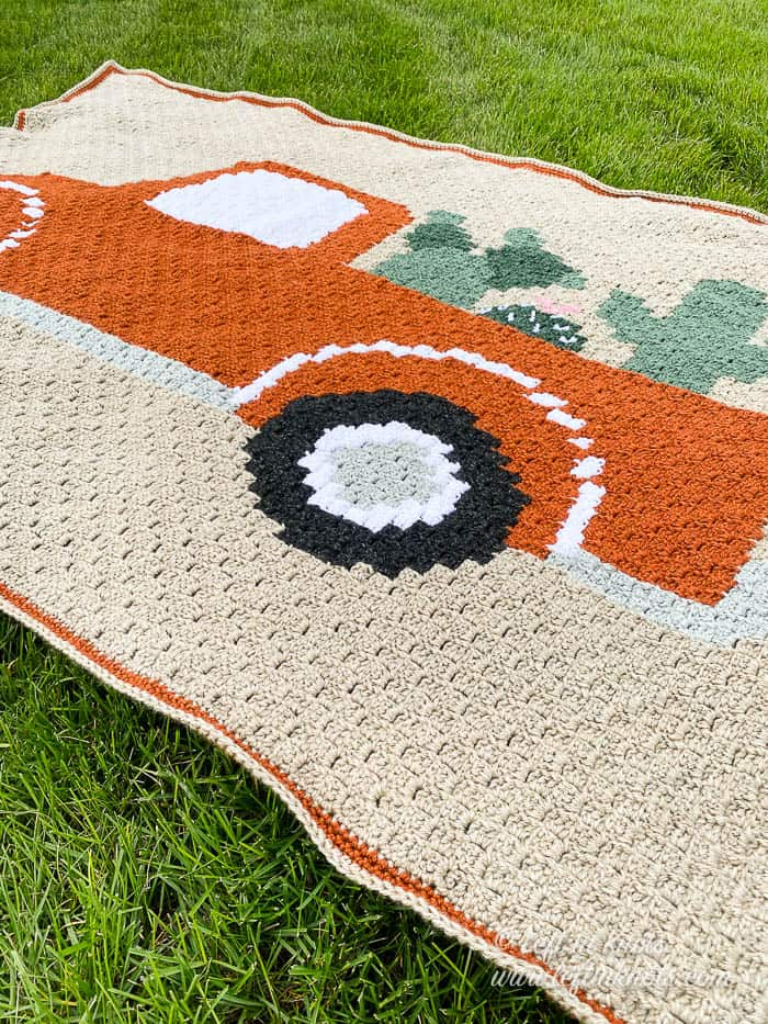 A crochet blanket of a vintage truck and plants