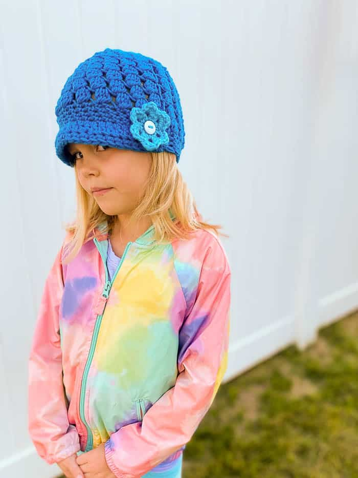 Blue crochet beanie with a small brim and flower accent